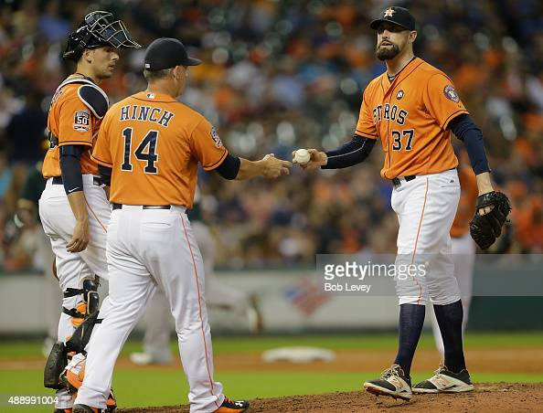 Pat Neshek of the Houston Astros hands the ball to manager AJ Hinch in the eighth inning as he leaves the game against the Oakland Athletics at...