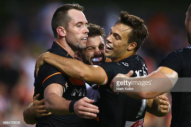 Pat Richards celebrates with his team mates James Tedesco and Luke Brooks of the Tigers after scoring a try during the round two NRL match between...