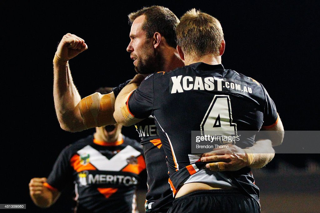 Pat Richards of the Tigers celebrates with team mate Chris Lawrence after scoring a try during the round 16 NRL match between the Wests Tigers and the Canberra Raiders at Campbelltown Sports Stadium on June 28, 2014 in Sydney, Australia.