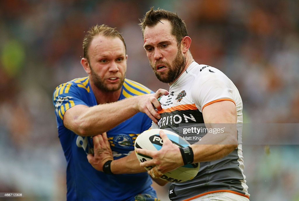 Pat Richards of the Tigers puts a fend on David Gower of the Eels during the round five NRL match between the Parramatta Eels and the Wests Tigers at ANZ Stadium on April 6, 2015 in Sydney, Australia.