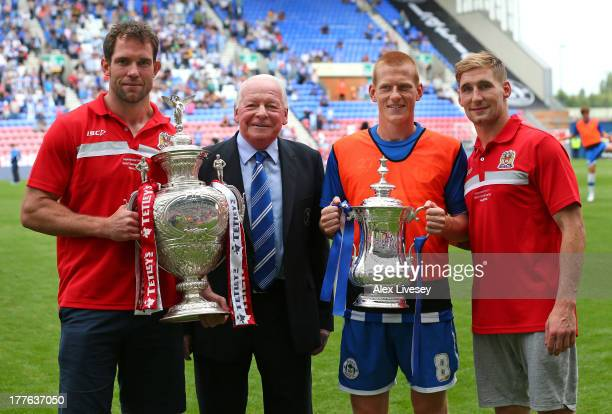 Pat Richards of Wigan Warriors Dave Whelan the chairman of Wigan Athletic Ben Watson of Wigan Athletic and Sam Tomkins of Wigan Warriors show off the...