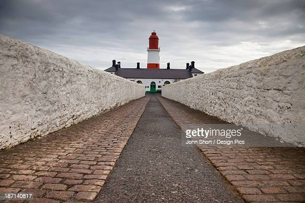 A Path Leading To A Red And White Lighthouse