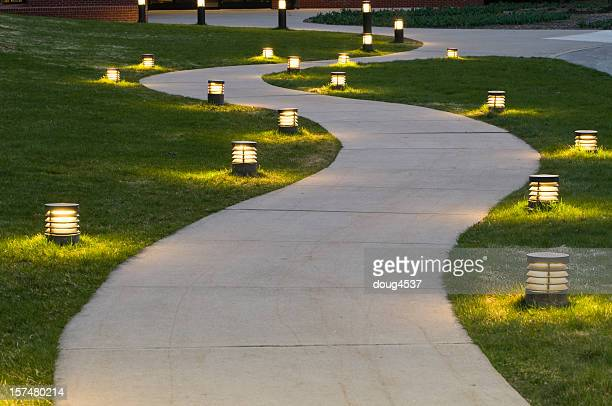 A path through the grass lit by lanterns