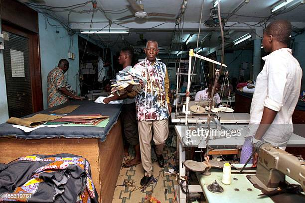 Pathe Ouedraogo aka Pathe 'O Burkina Faso born tailor of Nelson Mandela walks while holding shirts on December 11 2013 in his workshop in the...