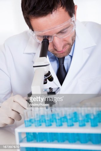 Pathologist or lab technician using a microscope : Stock Photo