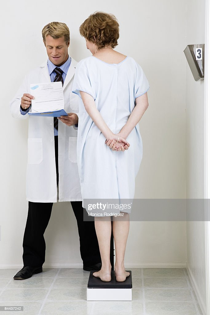 Patient and Doctor at weight scale : Stock Photo