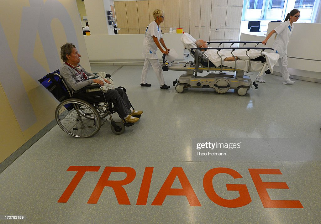A patient and health care professionals walk through the triage department at the Unfallkrankenhaus Berlin (UKB) hospital in Marzahn district on June 17, 2013 in Berlin, Germany. The UKB hospital has among the most modern emergency care services in Germany.