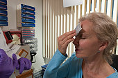 Patient applying ice on her forehead after injectable treatment