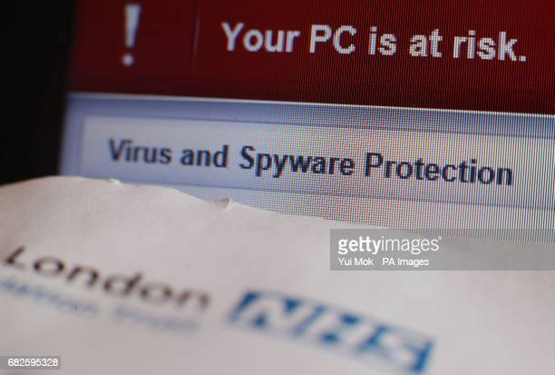 A patient appointment letter from a London NHS hospital next to a virus and spyware warning message on a laptop screen at a home in London following...
