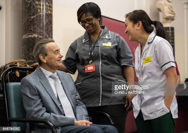 Patient Brian Paul waits with healthcare staff before meeting Britain's Prince Charles Prince of Wales during his visit to St Thomas's Hospital in...