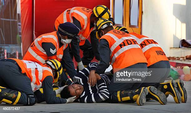 Patient carried on a stretcher into an ambulance during a Mock earthquake rescue drill at India International Trade Fair on November 18 2013 in New...