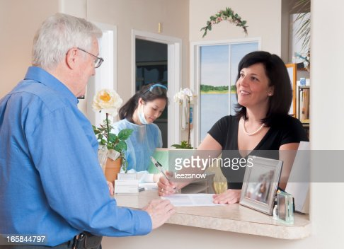 Patient Checking In At Reception For A Medical Appointment
