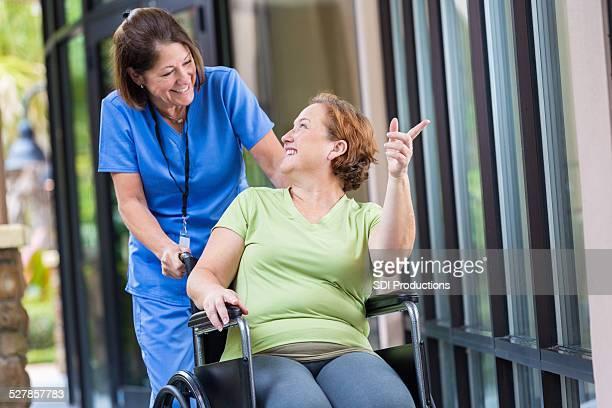 Patient Regeln Krankenschwester, während Sie sich im Rollstuhl geschoben Korridor hinunter