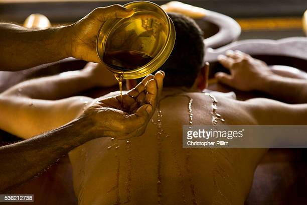 A patient has warm medicated oil poured over his whole body to prepare him for body massage as part of the overall Ayurveda experience at Kalari...