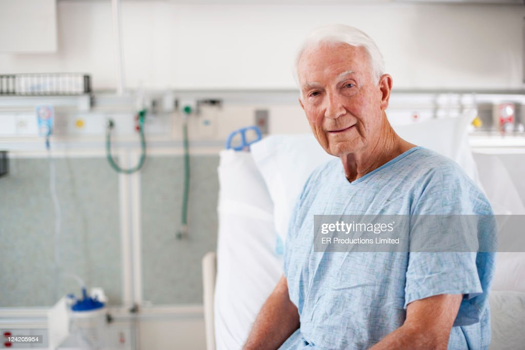 Patient in hospital gown sitting in hospital bed