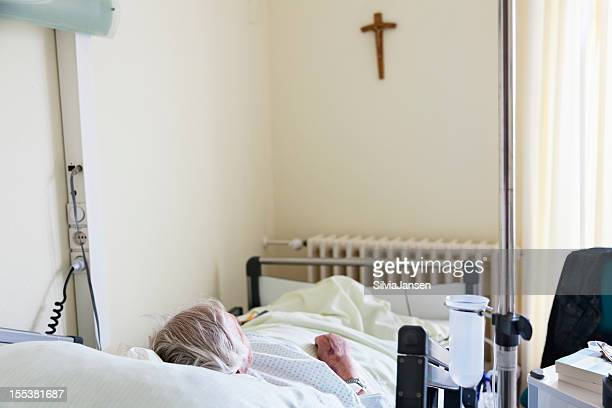 Patienten im Krankenhaus mit Kreuz an der Wand