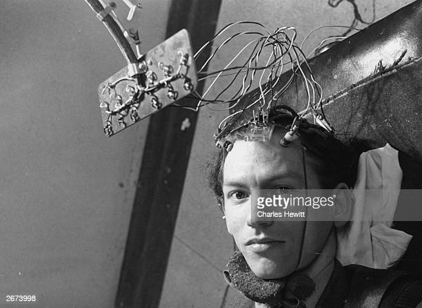 A patient is connected to an encephalogram machine which will record his brain's activity by reading the rhythmic electric pulses it emits This takes...