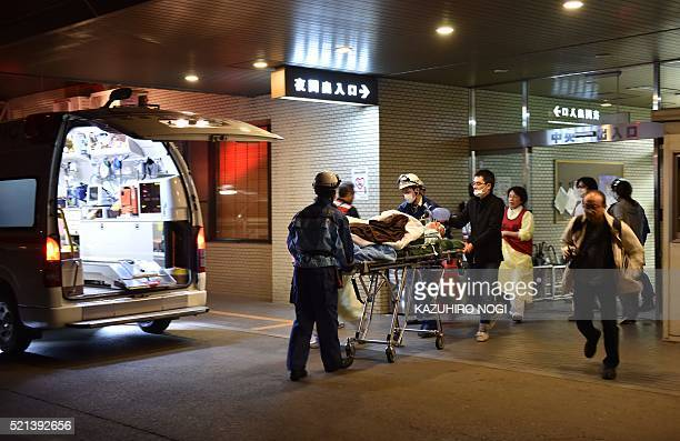 A patient is evacuated by emergency staff from an hospital in Kumamoto City on April 16 over fears it could collapse as a wave of aftershocks shook...