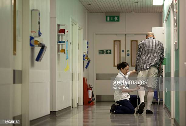 A patient is monitored by a nurse while walking on crutches along a corridor at Guy's Hospital on June 14 2011 in London England Prime Minister David...