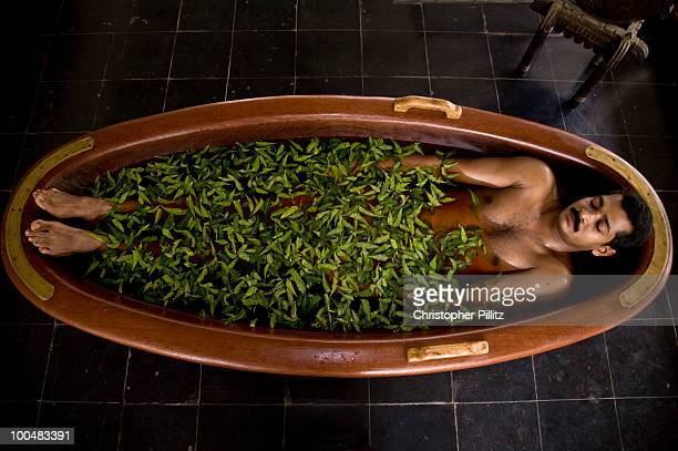A patient lies in a herb infused tub of water