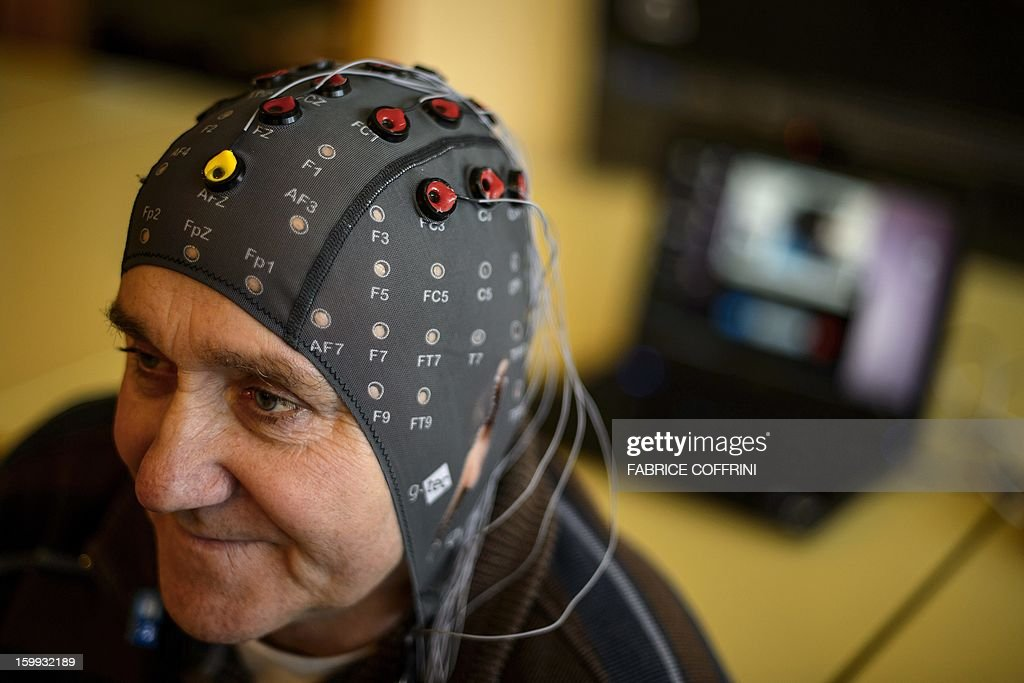 Patient Marc Andre Duc wears a cap with electrods next to a computer during a presentation of brain-machine interface by the Swiss Federal Institutes of Technology of Lausanne (EPFL) on January 23, 2013 in Sion. More than one hundred patients suffering from severe motor impairments have voluntarily participated in the development of non-invasive brain-machine interfaces. The main purpose of TOBI Eiuropean research program is to allow the patients either regain some of their mobility or improve their social relationships. AFP PHOTO / FABRICE COFFRINI