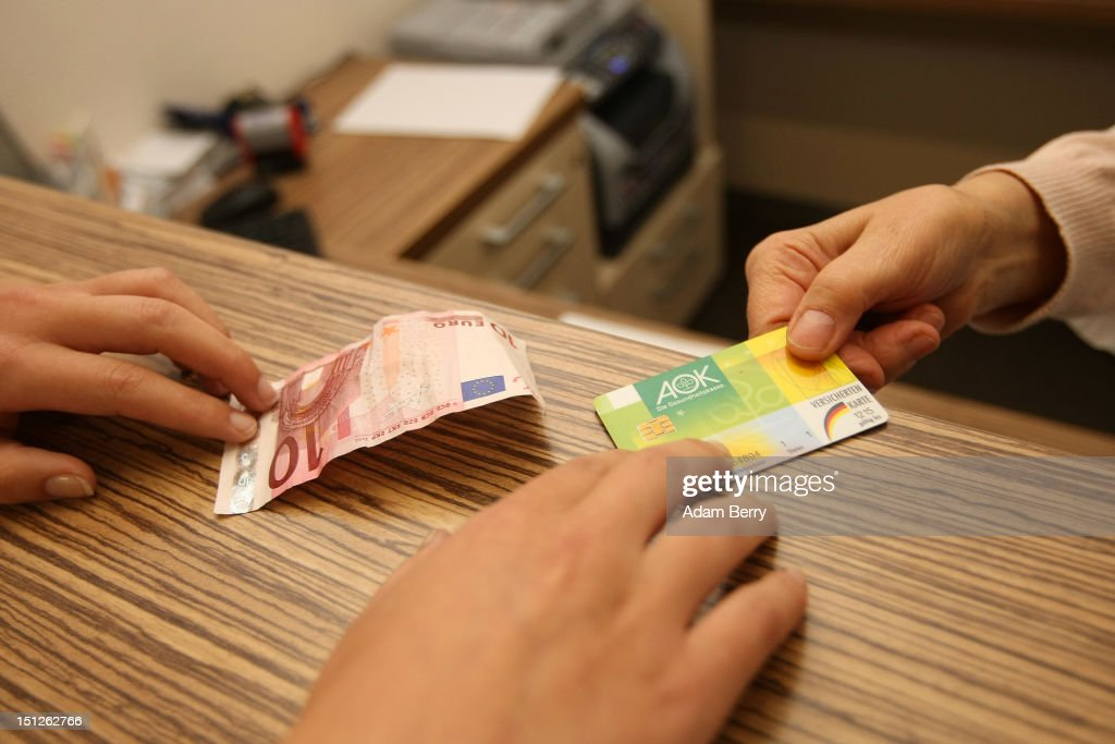A patient pays a quarterly consultion fee while handing her Allgemeine Ortskrankenkasse (AOK) health insurance card to a nurse on September 5, 2012 in Berlin, Germany. Doctors in the country are demanding higher payments from health insurance companies (Krankenkassen). Over 20 doctors' associations are expected to hold a vote this week over possible strikes and temporary closings of their practices if assurances that a requested additional annual increase of 3.5 billion euros (4,390,475,550 USD) in payments are not provided. The Kassenaerztlichen Bundesvereinigung (KBV), the National Association of Statutory Health Insurance Physicians, unexpectedly broke off talks with the health insurance companies on Monday.