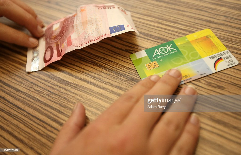 A patient pays a quarterly consultion fee while handing over her Allgemeine Ortskrankenkasse (AOK) health insurance card on September 5, 2012 in Berlin, Germany. Doctors in the country are demanding higher payments from health insurance companies (Krankenkassen). Over 20 doctors' associations are expected to hold a vote this week over possible strikes and temporary closings of their practices if assurances that a requested additional annual increase of 3.5 billion euros (4,390,475,550 USD) in payments are not provided. The Kassenaerztlichen Bundesvereinigung (KBV), the National Association of Statutory Health Insurance Physicians, unexpectedly broke off talks with the health insurance companies on Monday.