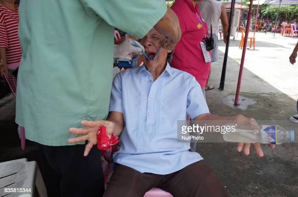 A patient reacts as he is injected with dental anaesthesia by a dentist prior to a tooth extraction during a medical mission at a village in Quezon...