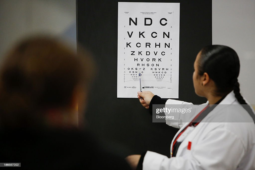 A patient receives a vision test during the Care Harbor Public Health Clinic event at the Los Angeles Sports Arena in Los Angeles, California, U.S., on Thursday, Oct. 31, 2013. The rate of uninsured Americans dropped slightly for the second consecutive year in 2012, a result of more people enrolling in Medicare and Medicaid, the U.S. Census Bureau reported Tuesday. Photographer: Patrick Fallon/Bloomberg via Getty Images