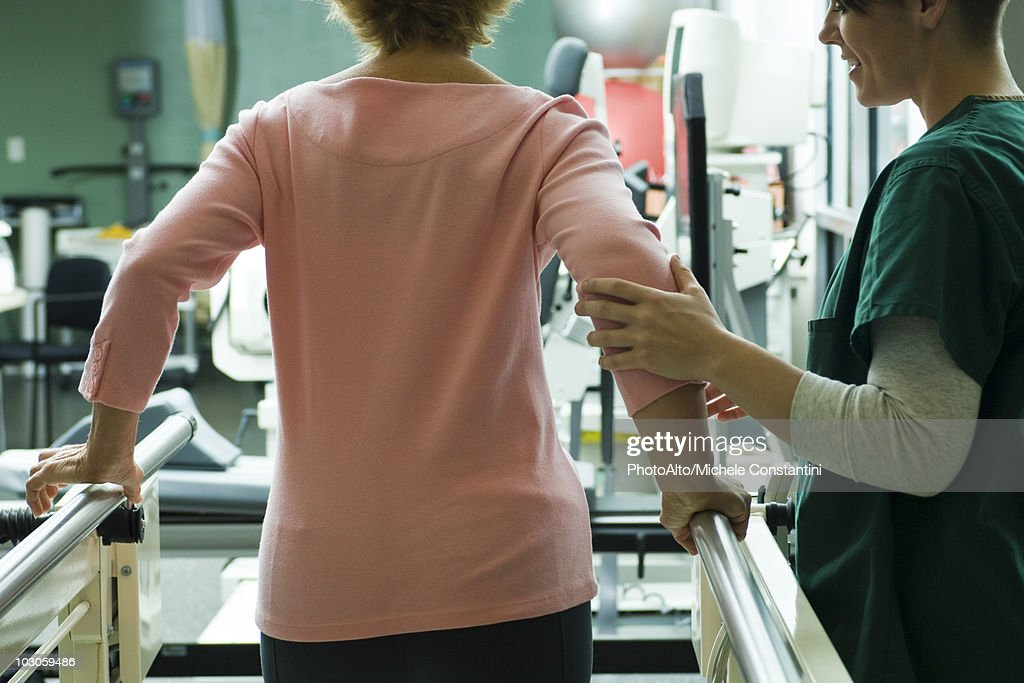Patient undergoing rehabilitation walking exercises with assistance from physical therapist