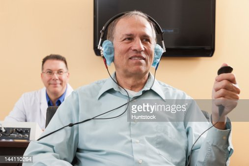 Patient using response button during audiometric evaluation : Stock-Foto