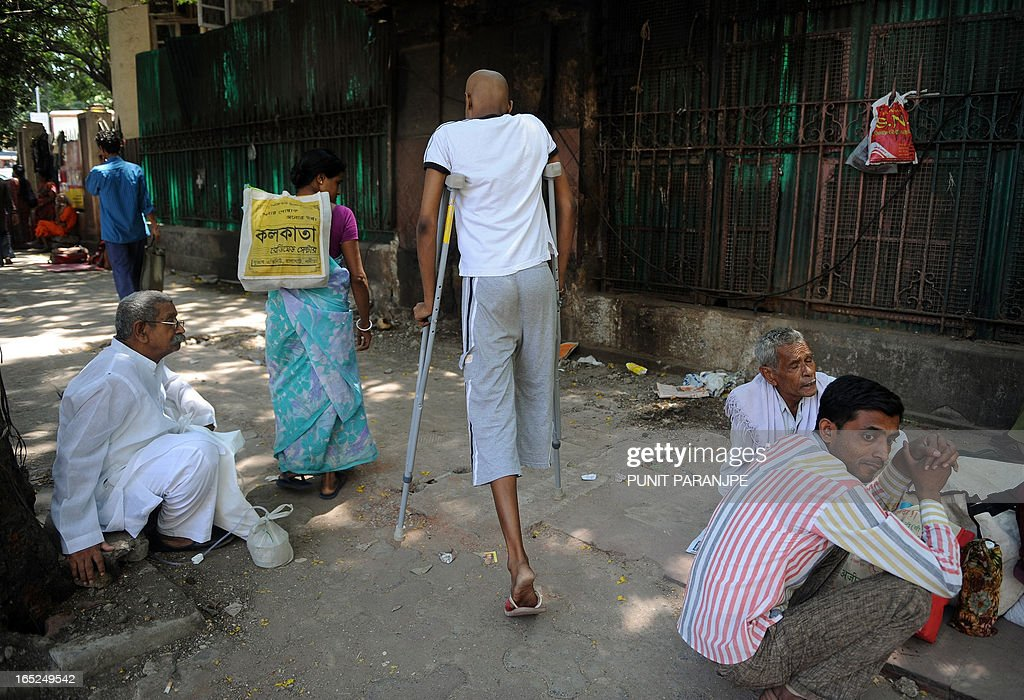 A patient (C) walks on crutches after visiting The Tata Memorial Hospital - specialist cancer treatment and research centre - in Mumbai on April 2, 2013. India's Supreme Court has rejected a patent bid by Swiss drug giant Novartis in a landmark ruling that activists say will protect cheap generic drugs and save lives in developing nations.