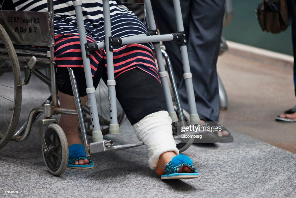 A patient with a bandaged leg sits in a wheelchair outside the International Patient Lounge of the Indraprastha Apollo Hospitals facility, operated by Apollo Hospitals Enterprise Ltd., in New Delhi, India, on Wednesday, July 19, 2013. Prathap C. Reddy, the cardiologist who built the Apollo hospital chain valued at $2 billion over three decades in India, says hes seeking growth overseas as the nations visa policies drive medical tourists to rivals. Photographer: Prashanth Vishwanathan/Bloomberg via Getty Images