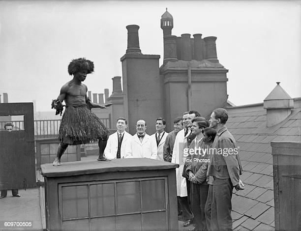 Patients and staff watch a west African 'witch doctor' or shaman of the Mende people performing a traditional dance on the roof of the Dreadnought...