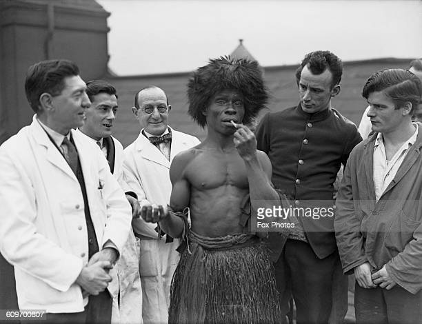 Patients and staff watch a west African 'witch doctor' or shaman of the Mende people eating glass on the roof of the Dreadnought Seamen's Hospital in...