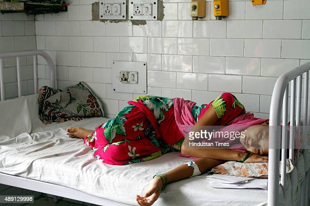 Patients await for routine checkup as they lie under a mosquito net inside a dengue ward of a government hospital on September 19 2015 in New Delhi...
