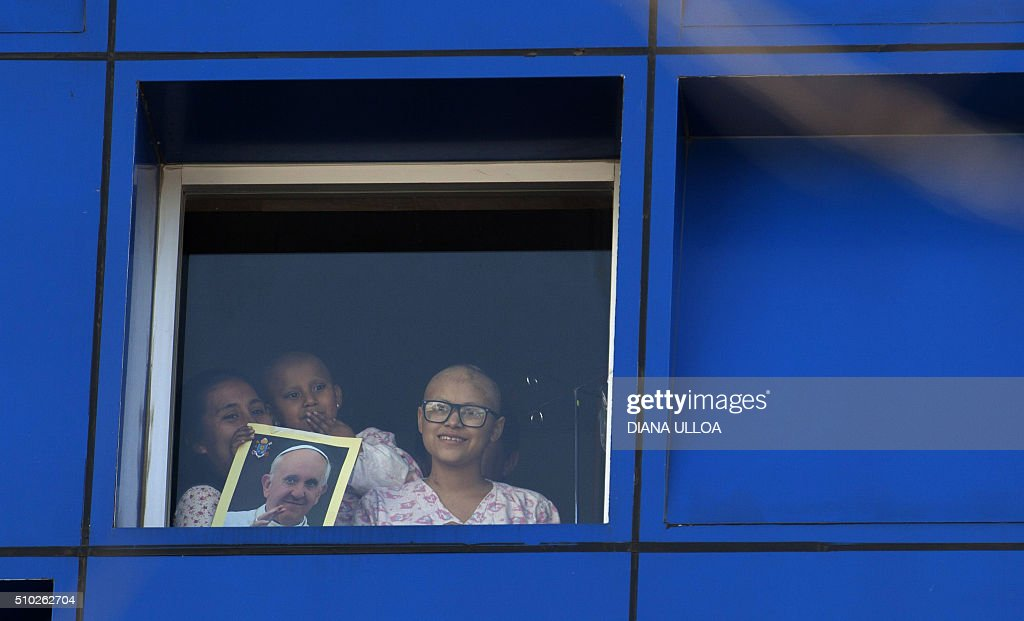 Patients from the Children Pediatric Hospital Federico Gomez watch from a widow the faithful waiting for the arrival of Pope Francis, in Mexico City on February 14, 2016. Pope Francis urged Mexicans on Sunday to turn their country into a land of opportunity where there is no need to emigrate or mourn victims 'of the merchants of death.'AFP PHOTO . AFP PHOTO /DIANA ULLOA / AFP / DIANA ULLOA