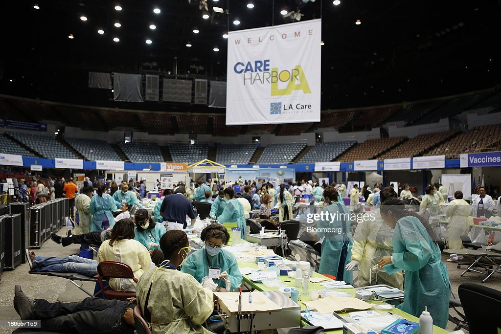 Patients receive dental care during the Care Harbor Public Health Clinic event at the Los Angeles Sports Arena in Los Angeles, California, U.S., on Thursday, Oct. 31, 2013. The rate of uninsured Americans dropped slightly for the second consecutive year in 2012, a result of more people enrolling in Medicare and Medicaid, the U.S. Census Bureau reported Tuesday. Photographer: Patrick Fallon/Bloomberg via Getty Images