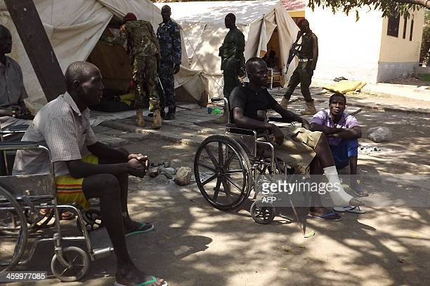 Patients sit on wheelchairs after receiving treatment at the Malakal Hospital in the Upper Nile State of South Sudan on December 31 2013 following...