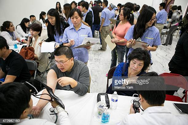 Patients talk to medical professionals and get their blood pressure measured at the general medical screening area during the Hsi Lai Temple Health...