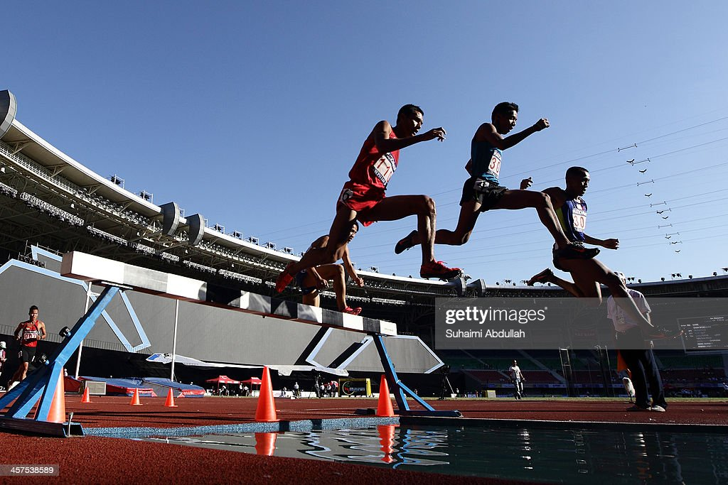 Patikarn Pechsricha of Thailand, Christoper Jr Ulboc of Philippines and Rene Herrera of Philippines compete in the men's 3000m steeplechase final during the 2013 Southeast Asian Games at Wunna Theikdi Stadium on December 18, 2013 in Nay Pyi Taw, Burma.