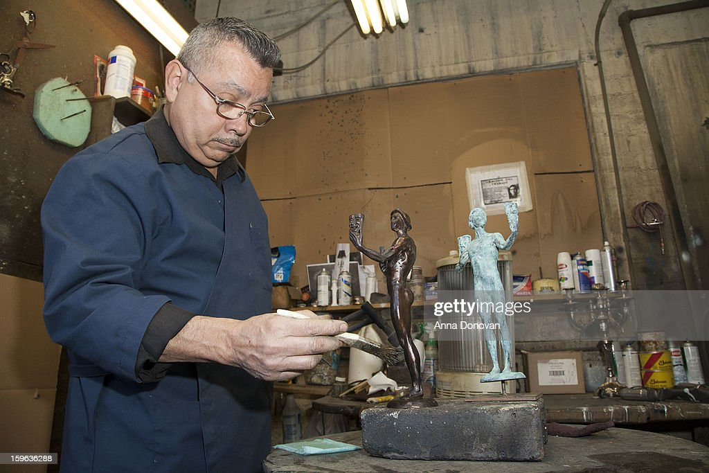 Patina artist Joaquin Quintero puting a finishing touch on one of the bronze Screen Actors Guild Award statuettes at the American Fine Arts Foundry on January 17, 2013 in Burbank, California.
