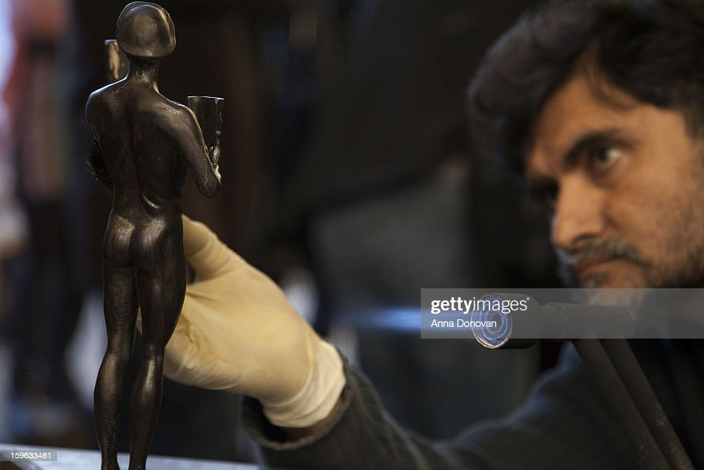 Patina artist Ricardo Godinez puting a finishing touch on one of the bronze Screen Actors Guild Award statuettes at the American Fine Arts Foundry on January 17, 2013 in Burbank, California.