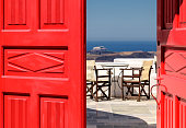 Red door open with view of patio and blue sea.
