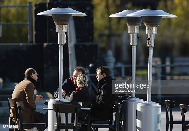 Patio heaters stand at a outside cafe as people's enjoy the sun on November 17 2008 in Berlin Germany Five Berlin districts have agreed to ban patio...