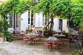 Open restaurant terrace under a grape vine in Saint-Emilion town, Gironde, France