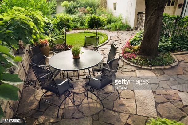 Patio with Flower Garden and Furniture in Backyard Stone Landscaping