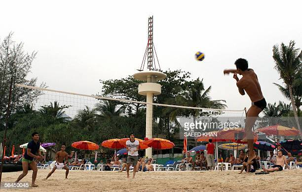 Western tourists and locals play beach volleyball ball close to the tsunami warning tower at Patong beach in southern Phuket province of Thailand 18...