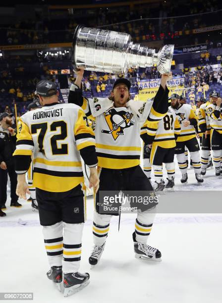 Patric Hornqvist and Carl Hagelin of the Pittsburgh Penguins celebrate with the Stanley Cup following a victory over the Nashville Predators in Game...