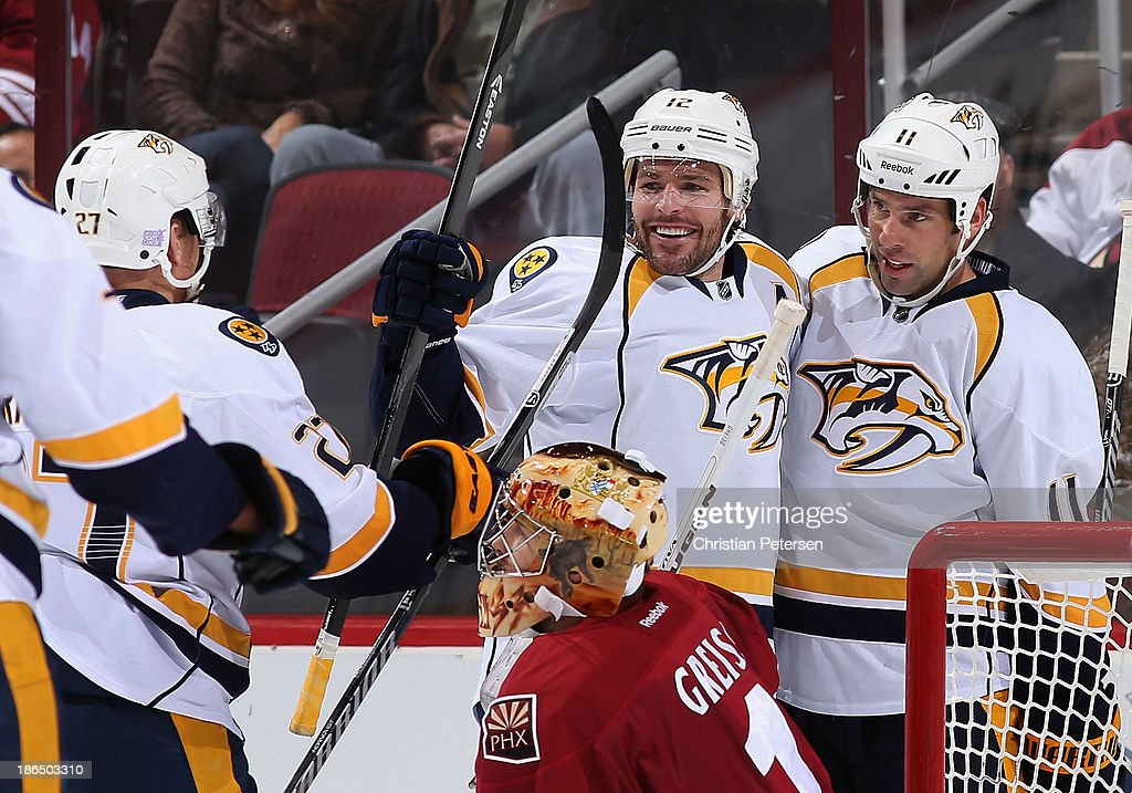 Patric Hornqvist #27, Mike Fisher #12 and David Legwand #11 of the Nashville Predators celebrate after Legwand scored a first period power play goal against goaltender Thomas Greiss #1 of the Phoenix Coyotes during the NHL game at Jobing.com Arena on October 31, 2013 in Glendale, Arizona.